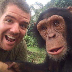 Chris Knight holds hands with a young chimpanzee.